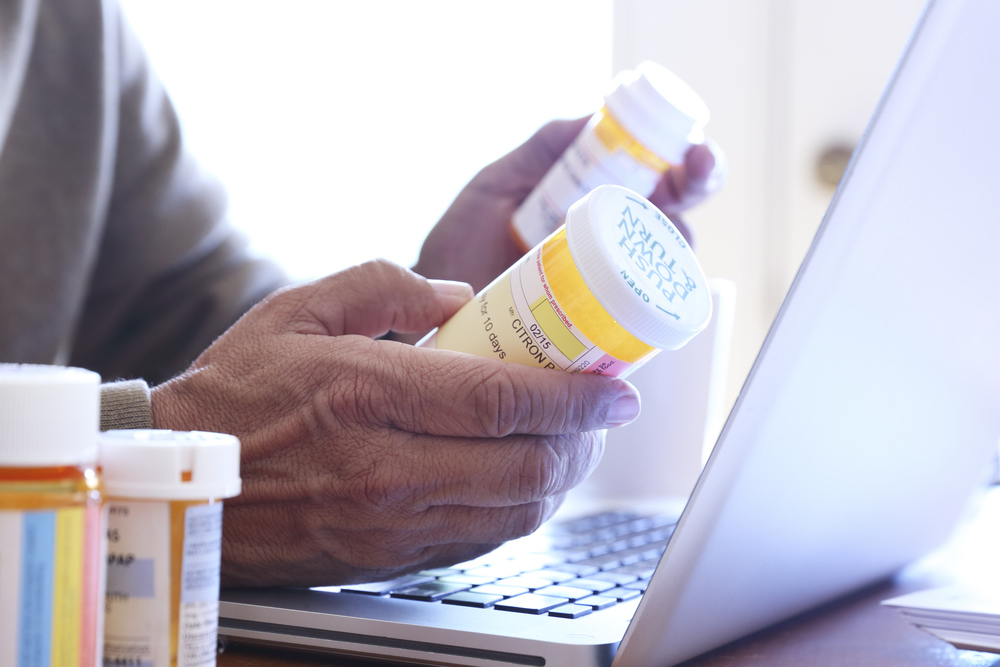 Close up of a Hispanic man in his late fifties holding two of his prescription medication bottles in his hands as he looks at his laptop computer while he sits at his dining room table. Sunlight filters in through the window behind him bathing the room with a soft glow of light.