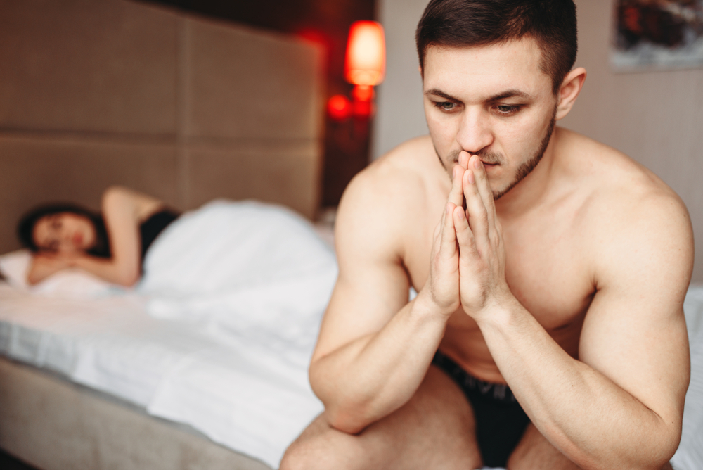 man with performance anxiety at the edge of the bed